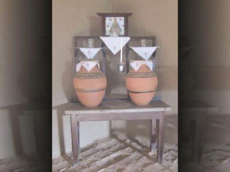 Móvel da sala de visita com potes, copos e água para matar a sede.